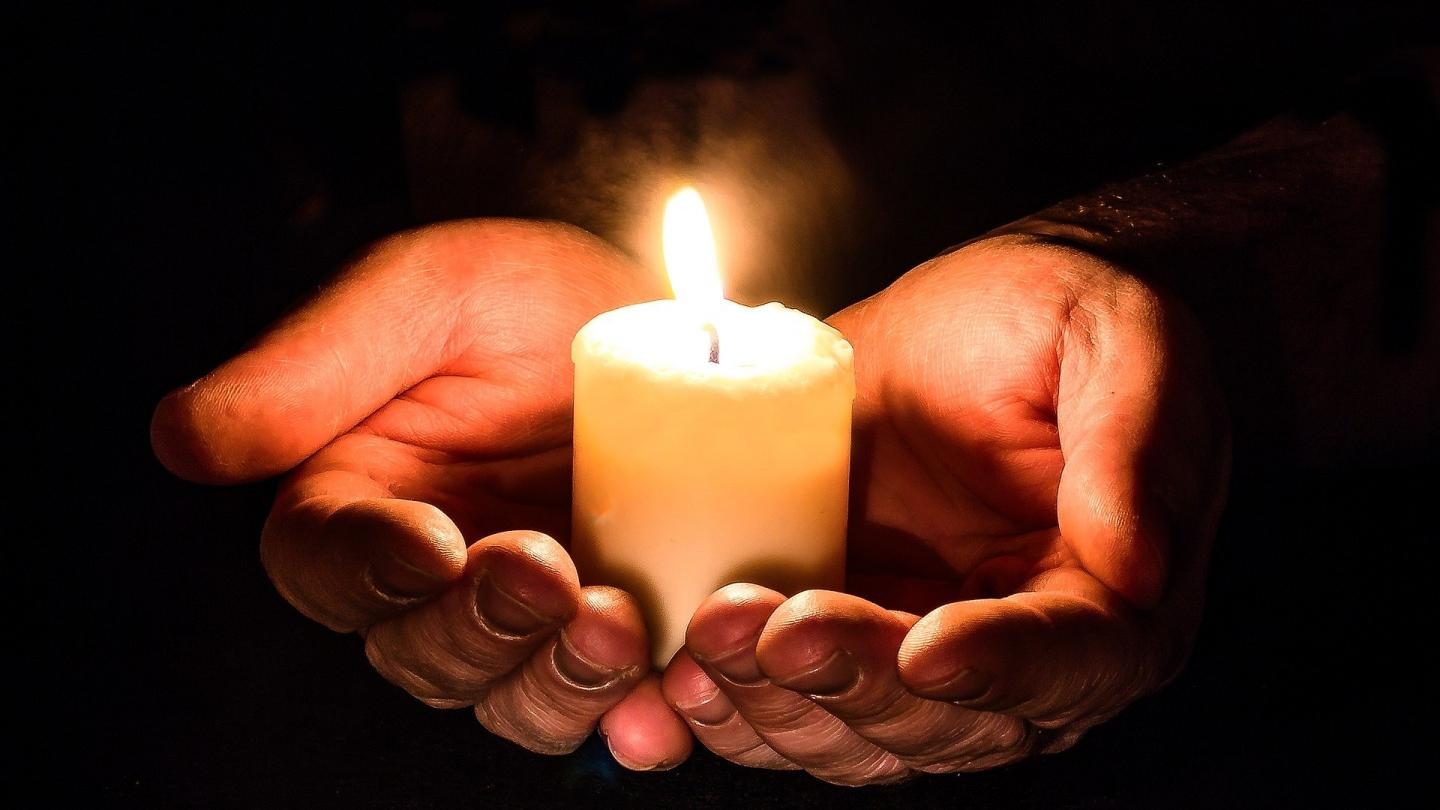 Hands holding a lite candles
